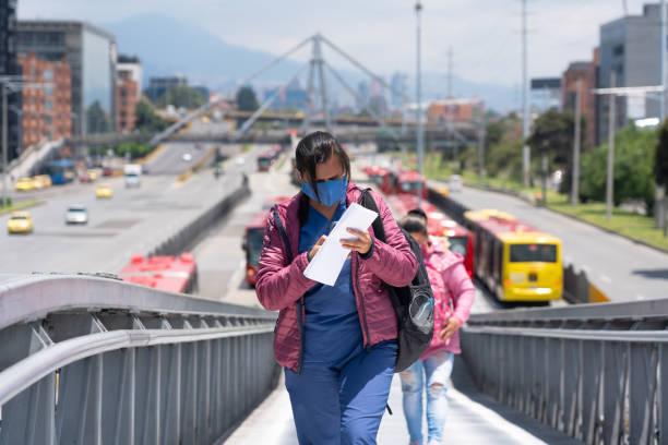 Frau mit Gesichtsmaske von einem öffentlichen Busbahnhof in Bogota. Kolumbien. – Foto