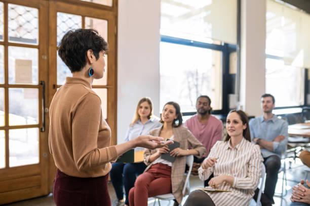 vrouwelijke docent die presentatie geeft aan zakenlui - kleine groep mensen stockfoto's en -beelden