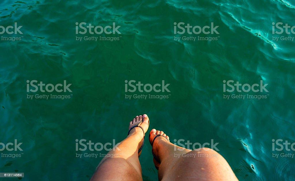 woman leg sitting over the sea stock photo