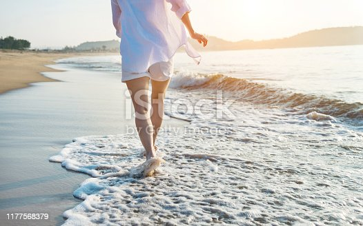 Woman leg walking on beach.