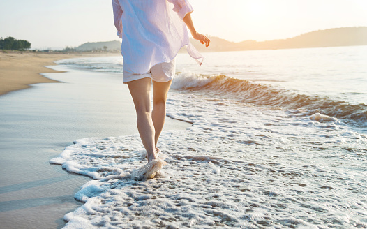 Woman leg walking on beach.