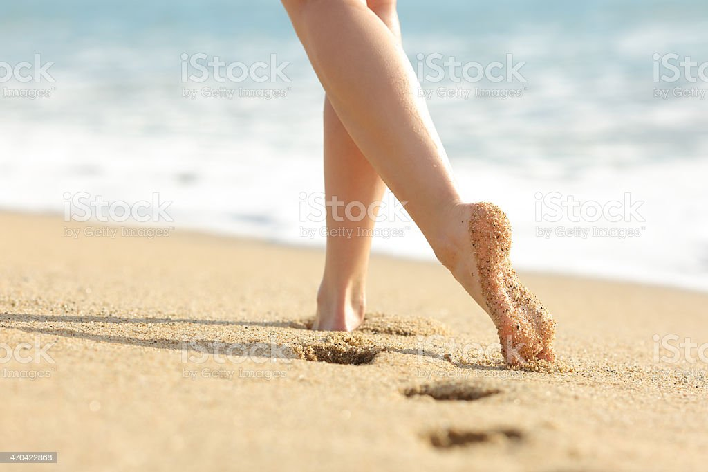 Woman legs and feet walking on the beach stock photo