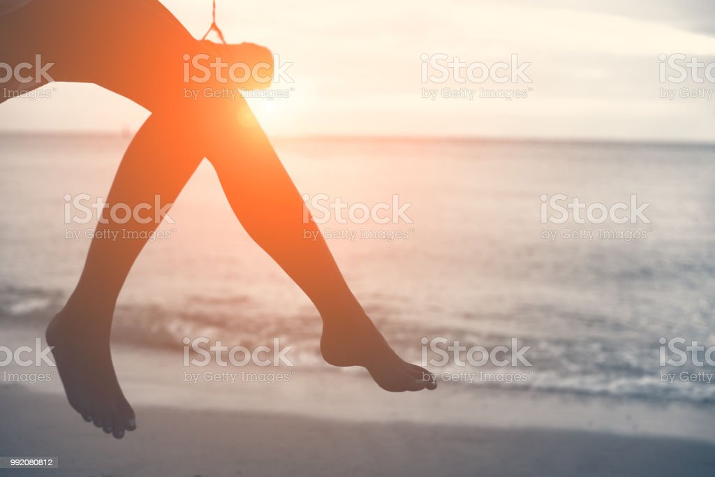 Woman legs at beach on wooden swing with sunset. Single woman concept. People and lifestyle concept. Lonely and sadness concept. Beach and sea theme. Finding soulmate theme. Copy space on right stock photo