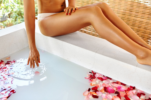istock Woman Legs. Body Care. Rose Flower Bath. Spa Skin Treatment. 530745588