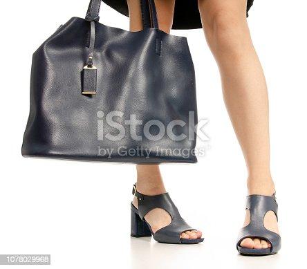 636803682 istock photo Woman legs feet black dress blue shoes blue purse bag 1078029968