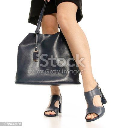 636803682 istock photo Woman legs feet black dress blue shoes blue purse bag 1078030126