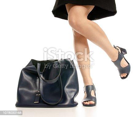 636803682 istock photo Woman legs feet black dress blue shoes blue purse bag 1078030168