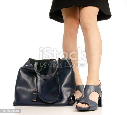 636803682 istock photo Woman legs feet black dress blue shoes blue purse bag 1078030382