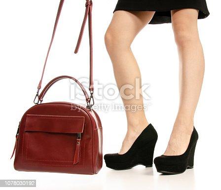 636803682 istock photo Woman legs feet black dress shoes red purse bag 1078030192