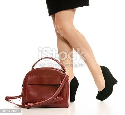 636803682 istock photo Woman legs feet black dress shoes red purse bag 1078030216