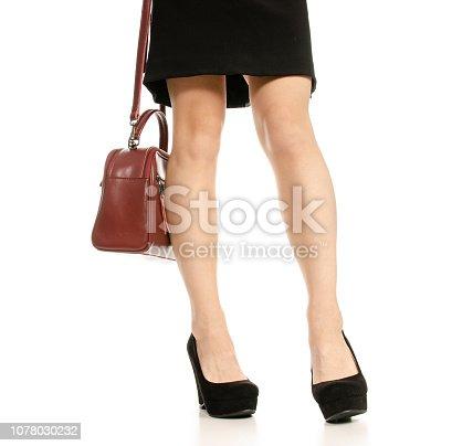 636803682 istock photo Woman legs feet black dress shoes red purse bag 1078030232