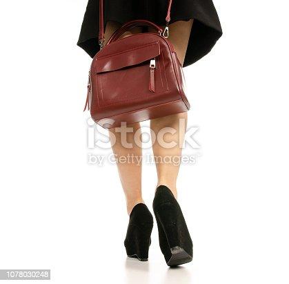 636803682 istock photo Woman legs feet black dress shoes red purse bag 1078030248
