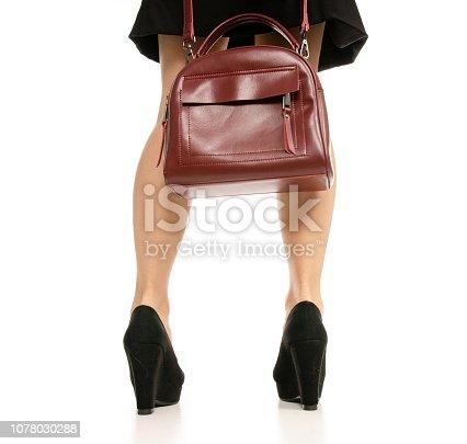 636803682 istock photo Woman legs feet black dress shoes red purse bag 1078030288