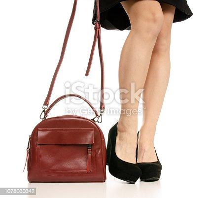 istock Woman legs feet black dress shoes red purse bag 1078030342
