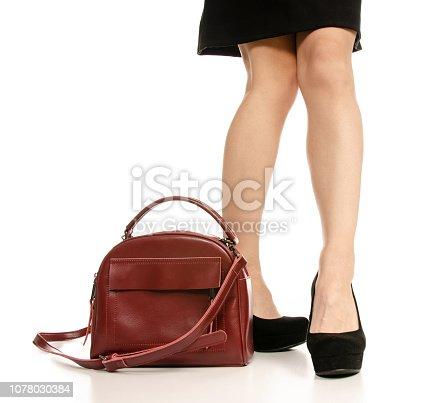 636803682 istock photo Woman legs feet black dress shoes red purse bag 1078030384