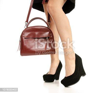636803682 istock photo Woman legs feet black dress shoes red purse bag 1078030402
