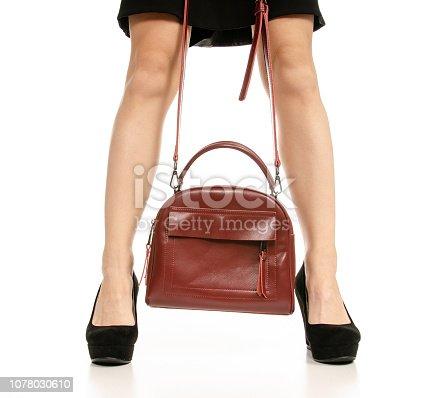 636803682 istock photo Woman legs feet black dress shoes red purse bag 1078030610