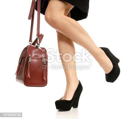 636803682 istock photo Woman legs feet black dress shoes red purse bag 1078030730