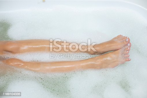 istock Woman legs in bath foam 1169104335
