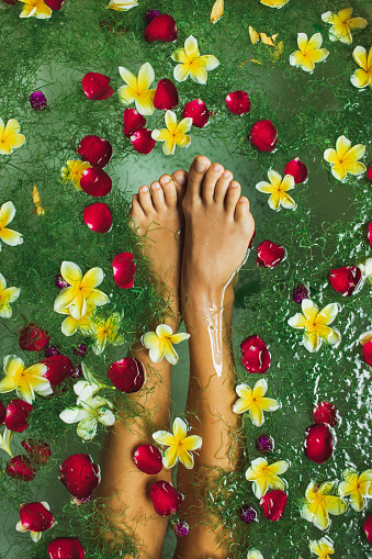 Woman legs in bath tub with tropical flowers, beauty spa treatment, pedicure, relaxation in hotel. Bali style. Rose red petals, yellow frangipani.