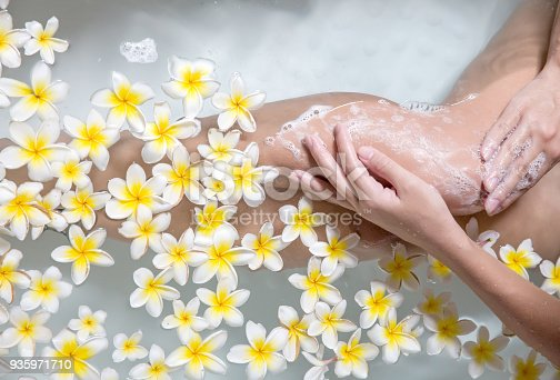 istock Woman legs in bath tube with flowers spa relaxation body care therapy 935971710