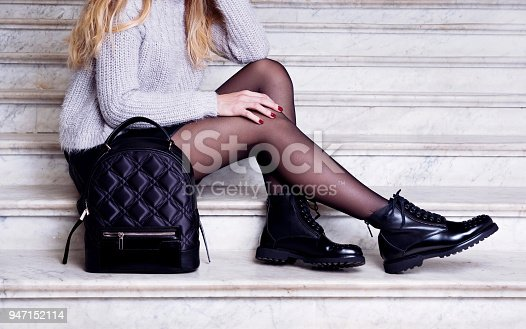 Woman legs in black ankle boots with bag. Trendy hipster outfit style
