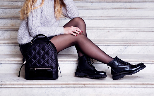 istock Woman legs in black ankle boots with bag. 947152114