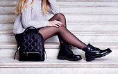 女性足黒の足首のブーツ バッグ。