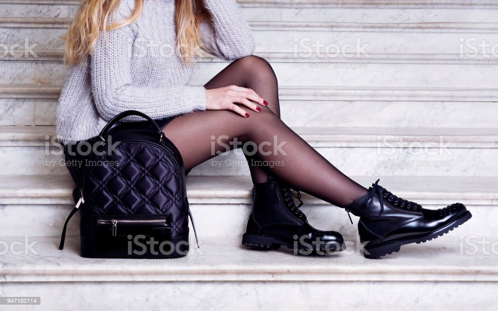 Woman legs in black ankle boots with bag. stock photo