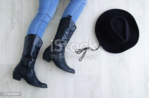Woman legs in black cowboy boots with a cowboy hat. Lying on a gray wooden background.