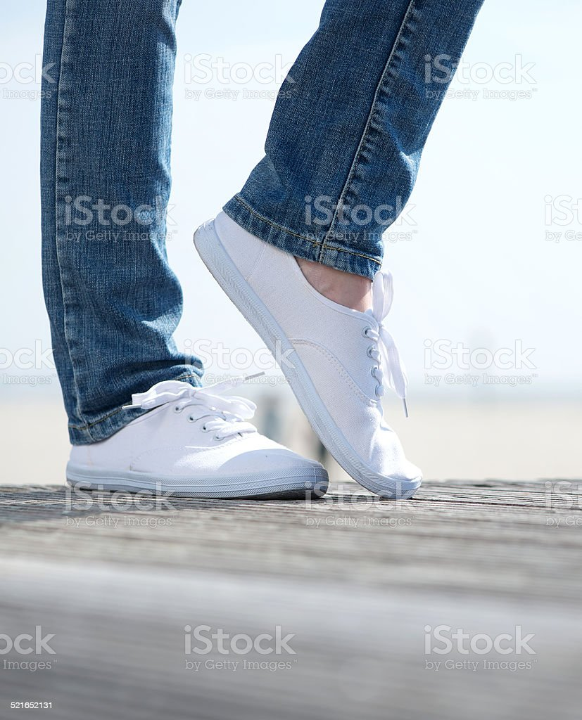 Woman legs in comfortable white shoes standing outdoors stock photo