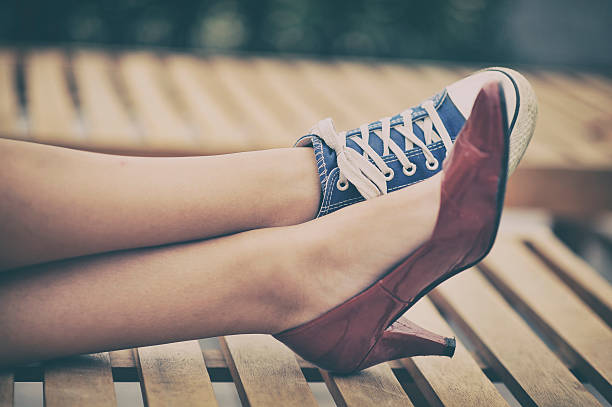 Woman legs in different shoes stock photo