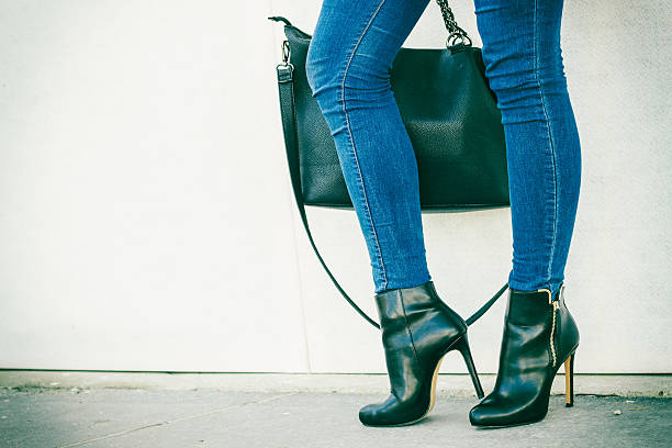 woman legs in heels shoes handbag in hand stock photo