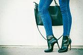 女性の足をヒール靴のハンドバッグを手に