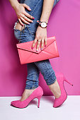 istock Woman legs in jeans with pink handbag  high heels shoes 539642822
