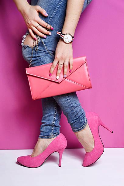 frau beine in jeans und rosa handtasche stöckel schuh - handtasche jeans stock-fotos und bilder
