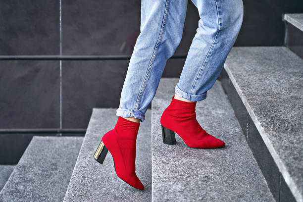 Woman legs in red sexy trendy stretch knitted fabric pointed toe block heel sock boots shoes and blue denim jeans pants stock photo