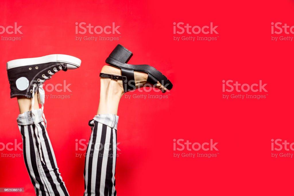 Pernas de mulher no verão sapatos isolados sobre fundo vermelho. - Foto de stock de Acessório royalty-free