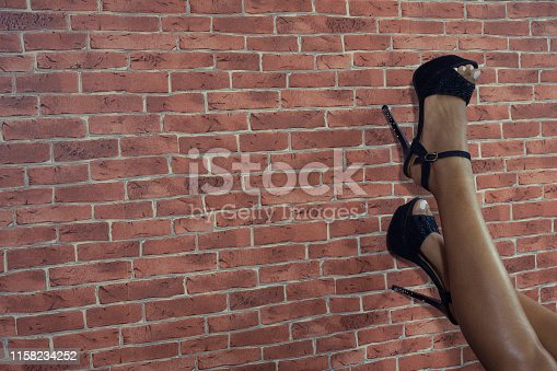 Woman legs on brick wall wearing black high heels