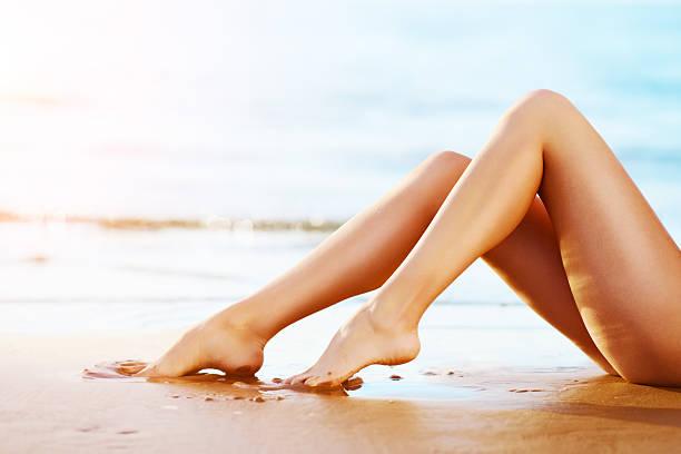 Woman legs on the sunset beach stock photo