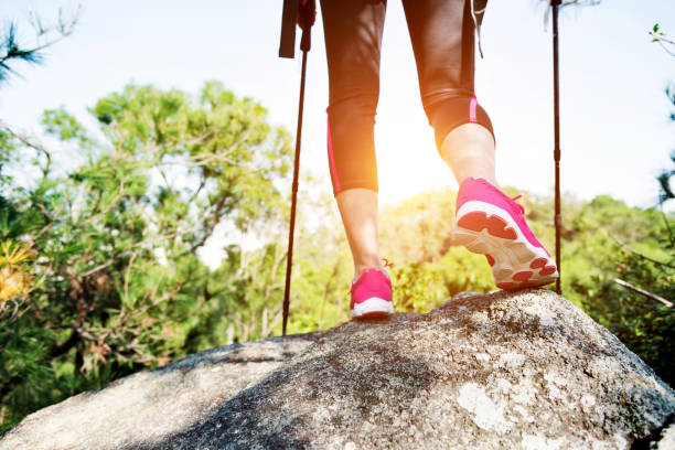 Woman legs on the top of mountain peak rock Woman legs on the top of mountain peak rock. nordic walking stock pictures, royalty-free photos & images