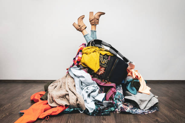 woman legs out of a pile of clothes on the floor. shopping addiction concept woman legs out of a pile of clothes on the floor. shopping addiction concept arrangement stock pictures, royalty-free photos & images