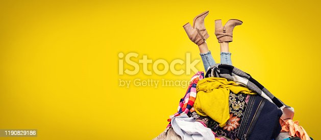 istock woman legs out of clothes pile on yellow background with copy space 1190829186
