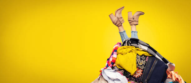 woman legs out of clothes pile on yellow background with copy space stock photo
