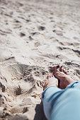 Woman tanned legs on sand beach. Travel concept.