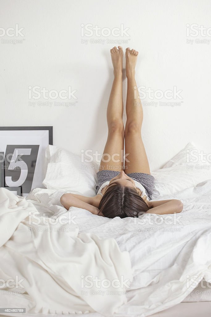Woman legs raised up high on bed. stock photo