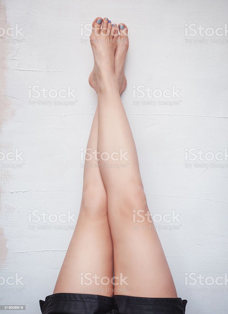 Woman legs raised up high on the wall stock photo