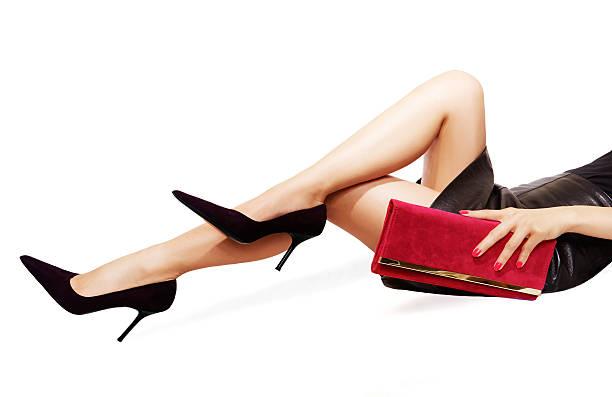 frau beine sexy schwarzen high-heels, roten handtasche. isoliert auf weiß. - schwarze hohe schuhe stock-fotos und bilder