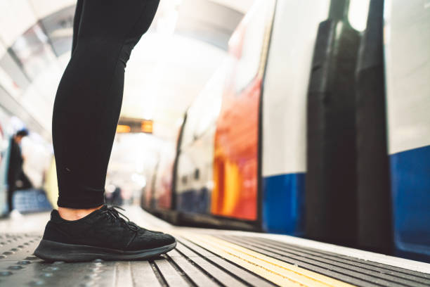 Woman legs standing on the line in London underground stock photo