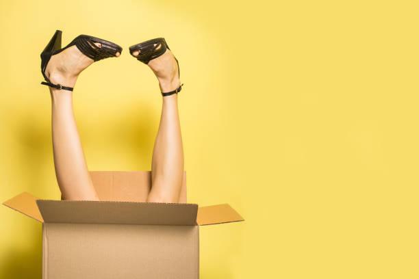 frau beine ragen aus karton - kleider günstig kaufen stock-fotos und bilder